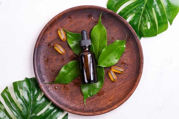 Schoonheids natuurlijke producten met omega 3 gelcapsules en serum in glazen flessen, groene bladeren op houten plaat op wit