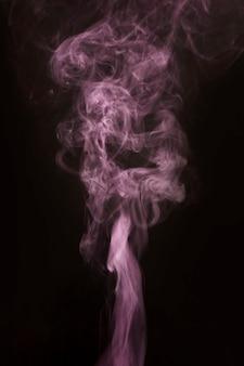 Schoonheids roze rook die zich omhoog op zwarte achtergrond beweegt