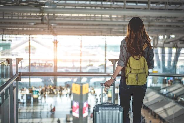 Schoonheids vrouwelijke toeristen die op vlucht wachten om bij luchthaven op te stijgen. mensen en levensstijlen