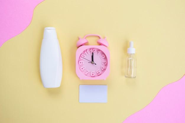 Schoonheidsachtergrond van cosmetische flessen en wekker op gele en roze papieren achtergrond. zomer huidverzorgingsconcept