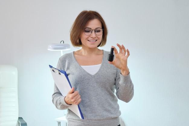 Schoonheidsbedrijf, werkende rijpe vrouweigenaar met klembord en nagelgellak, witte binnenruimte