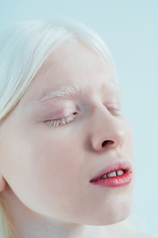 Schoonheidsbeeld van een albino-meisje dat in de studio poseert en lingerie draagt concept over body positivity diver