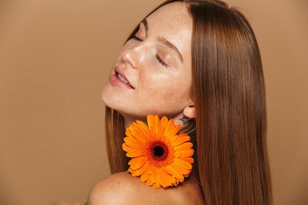 Schoonheidsbeeld van jonge shirtless vrouwen20s die zich met oranje bloem bevinden, die over beige achtergrond wordt geïsoleerd
