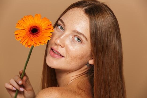 Schoonheidsbeeld van mooie shirtless vrouwen20s die zich met oranje bloem bevinden, die over beige achtergrond wordt geïsoleerd