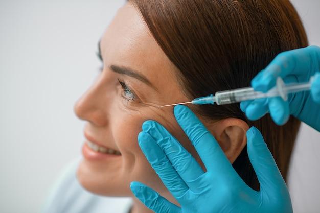 Schoonheidsbehandeling. een donkerharige vrouw van middelbare leeftijd die een mooie injectieprocedure ondergaat