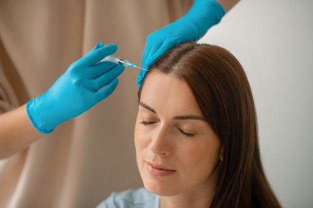 Schoonheidsbehandeling. een vrouw die met haar ogen dicht zit tijdens een schoonheidsbehandeling