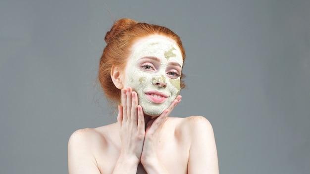 Schoonheidsbehandeling. het meisje dat een masker van groene klei toepast op het gezicht. esthetische procedure
