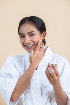 Schoonheidsbehandeling met vrouw houdt een vochtinbrengende crème in haar gezicht