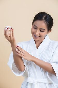 Schoonheidsbehandeling met vrouw houdt een vochtinbrengende crème in haar hand