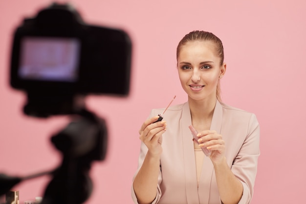 Schoonheidsblogger die de video maakt en haar volgers leert make-up te maken die op roze wordt geïsoleerd