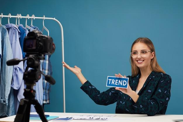 Schoonheidsblogger zittend aan tafel en wijzend op kleding, praat ze met volgers over de mode online