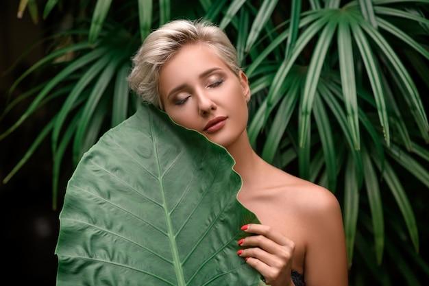 Schoonheidsblonde model met gesloten ogen. natuurlijke make-up en groene bladeren