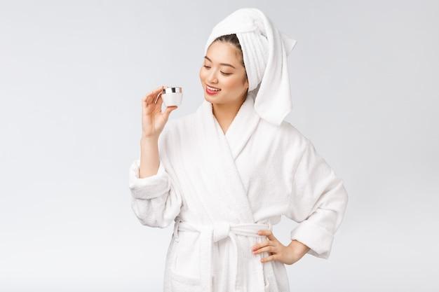 Schoonheidsconcept aziatische mooie vrouw die met perfecte huid kosmetische fles houden