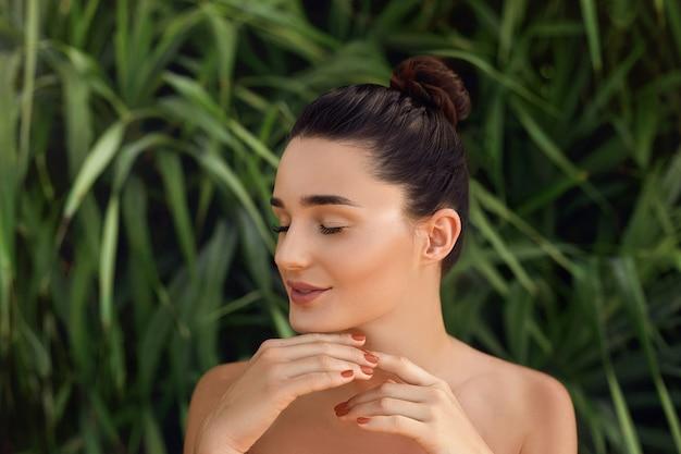 Schoonheidsconcept. mooi vrouwenmodel met perfecte schone huid. portret van meisje in tropische bladeren. lichaams- en huidverzorging.