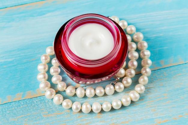Schoonheidscrème in een rode glazen pot met een parelketting op een blauwe houten plank