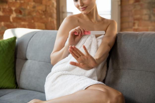 Schoonheidsdag. vrouw die een handdoek draagt die haar dagelijkse huidverzorging en manicure thuis doet. zittend op de bank ziet er gelukkig en kalm uit. concept van schoonheid, zelfzorg, cosmetica, jeugd, thuisweekend, spa.