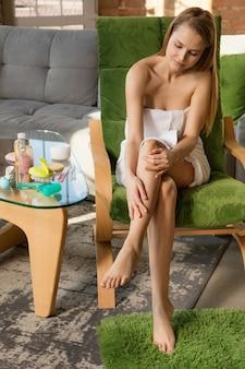 Schoonheidsdag. vrouw die een handdoek draagt die haar dagelijkse huidverzorgingsroutine thuis doet. hydrateren, anti-cellulitis, lymfedrainage massage. concept van schoonheid, zelfzorg, cosmetica, jeugd.