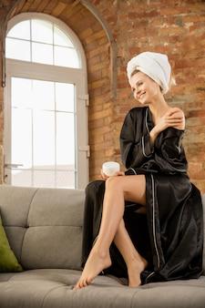 Schoonheidsdag vrouw in zijden gewaad die haar dagelijkse huidverzorgingsroutine thuis doet