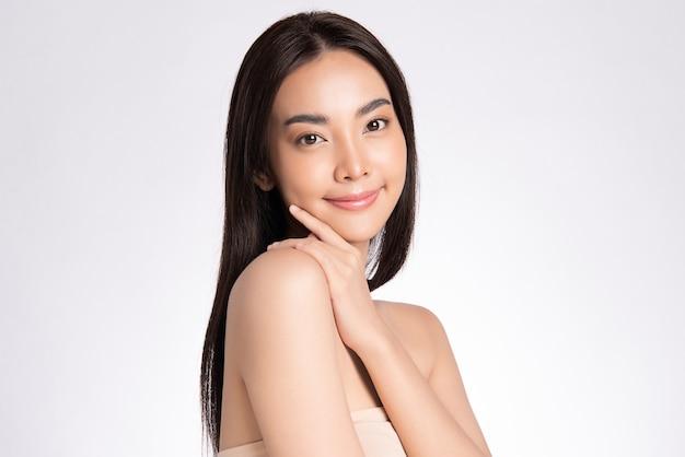 Schoonheidsgezicht glimlachende aziatische vrouw wat betreft gezond huidportret mooi gelukkig meisjesmodel met verse gloeiende gehydrateerde gezichtshuid en natuurlijke make-up