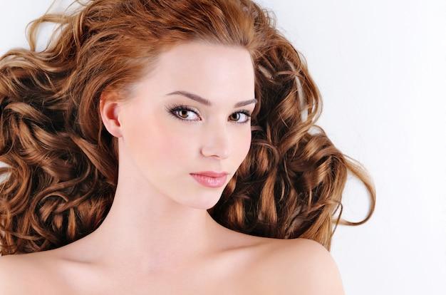 Schoonheidsgezicht van de aantrekkelijke jonge vrouw met krullende haren