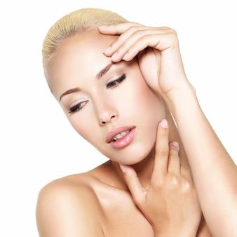 Schoonheidsgezicht van de jonge mooie blonde vrouw met handen