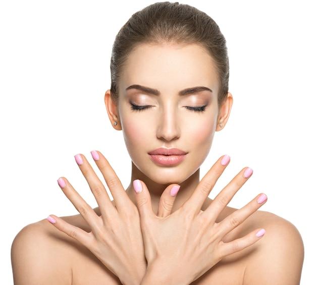 Schoonheidsgezicht van de jonge mooie vrouw - die op wit wordt geïsoleerd. vrouwtje met mooie vingernagel. vrij jong meisje toont handen vóór gezicht met roze spijkers