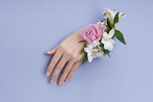 Schoonheidshand met bloemen in een gat in een purper document