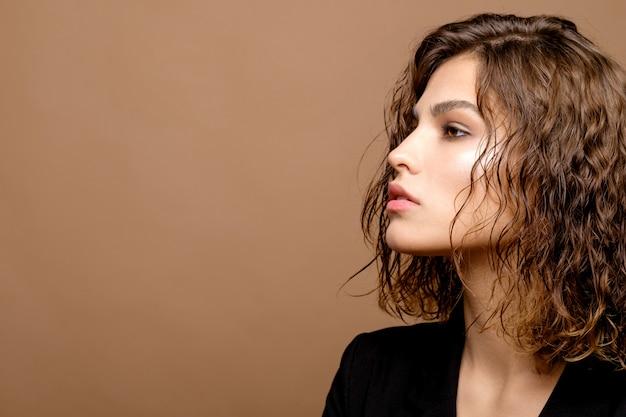 Schoonheidsmannequin met schone huid en krullend haar in zwart jasje op beige muur, ernstige bedrijfsvrouw, exemplaarruimte