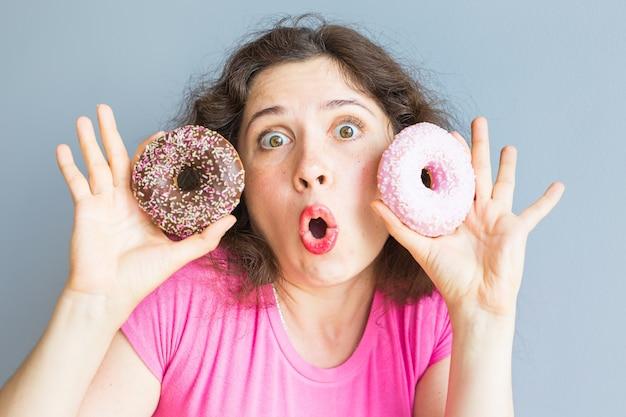 Schoonheidsmeisje die kleurrijke donuts nemen. grappige vrolijke vrouw met snoep, dessert. dieet, dieetconcept. junkfood, feest en feest.