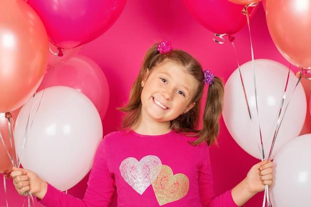 Schoonheidsmeisje die met kleurrijke luchtballons over roze glimlachen