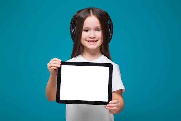 Schoonheidsmeisje in t-stukoverhemd en oortelefoons met de lange tablet van de haargreep