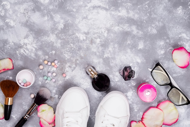 Schoonheidsmiddelen in parfum en schoenen op een grijze achtergrond met exemplaarruimte
