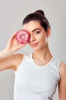 Schoonheidsmodel heeft een roze dessert. lach. eetpatroon. grappig. de donkerbruine vrouw proeft een toetje