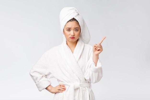 Schoonheidsportret die van jonge vrouw en vinger tonen richten aan lege exemplaar ruimte, aziatische schoonheid in badjas