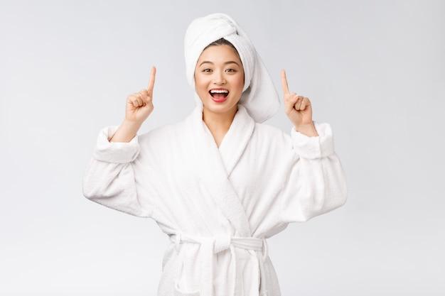 Schoonheidsportret die van jonge vrouw en vinger tonen richten aan lege exemplaar ruimte, aziatische schoonheid in badjas.
