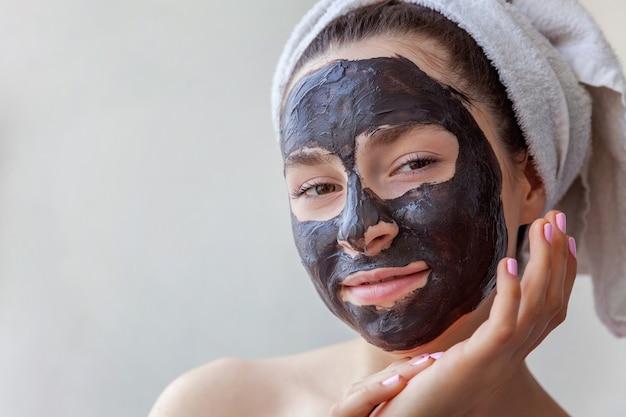 Schoonheidsportret die van vrouw in handdoek op hoofd zwart voedend masker op gezicht toepassen