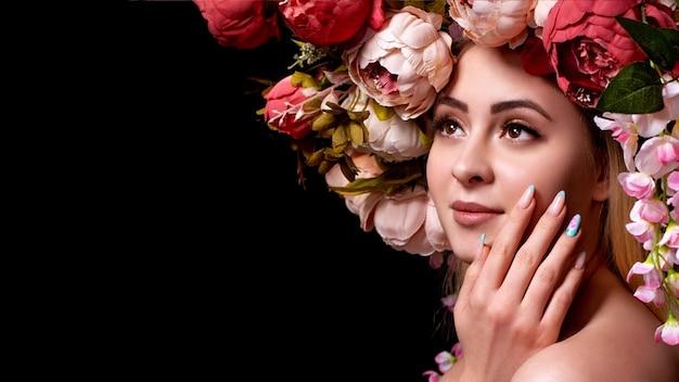Schoonheidsportret, meisjeshoofd in bloemen, op zwart.
