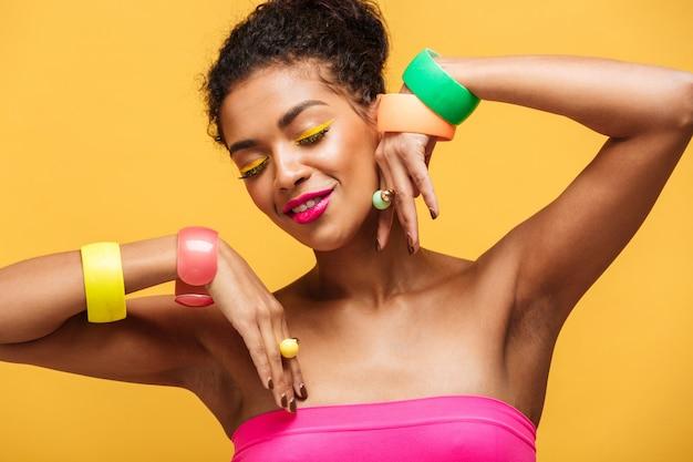 Schoonheidsportret van aantrekkelijke afrikaanse amerikaanse vrouw met maniermake-up en juwelen bij handen stellen geïsoleerd, over gele muur