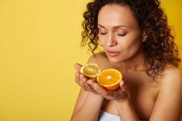Schoonheidsportret van aantrekkelijke gekrulde halfnaakte vrouw met natuurlijke make-up en gloeiende gehydrateerde gezichtshuid, genietend van citrusgeur in haar handen. geïsoleerd