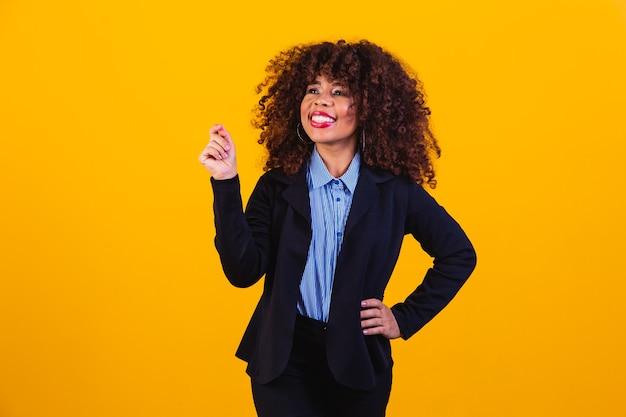 Schoonheidsportret van afrikaanse amerikaanse vrouw met afrokapsel en glamourmake-up. braziliaanse vrouw. gemengd ras. gekruld haar. haarstijl. gele achtergrond. afro-vrouw die naar de camera lacht