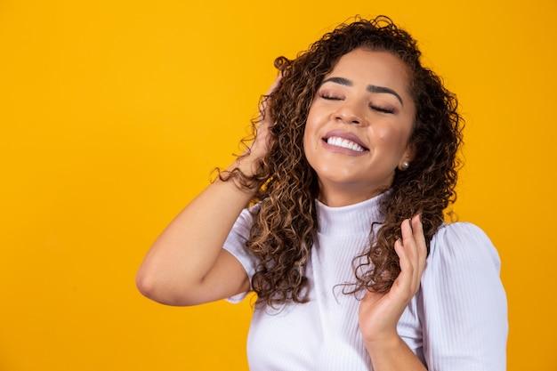 Schoonheidsportret van afrikaanse amerikaanse vrouw met afrokapsel en glamourmake-up. braziliaanse vrouw. gemengd ras. gekruld haar. haarstijl. gele achtergrond Premium Foto