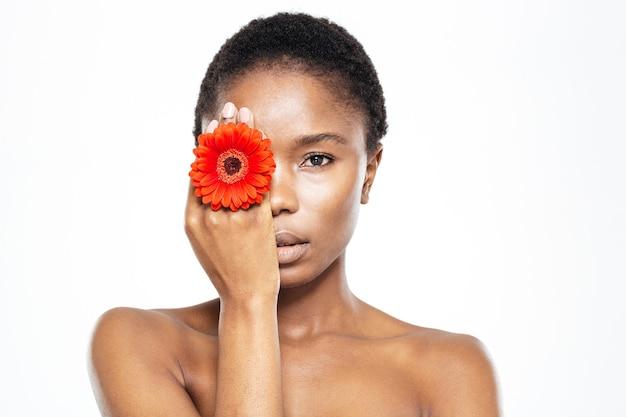 Schoonheidsportret van afro-amerikaanse vrouw die oog behandelen met bloem die op witte achtergrond wordt geïsoleerd