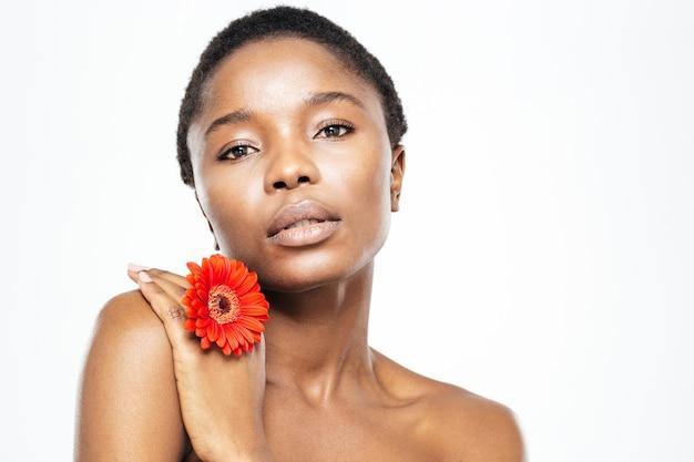 Schoonheidsportret van afro-amerikaanse vrouw met bloem die camera bekijkt die op witte achtergrond wordt geïsoleerd