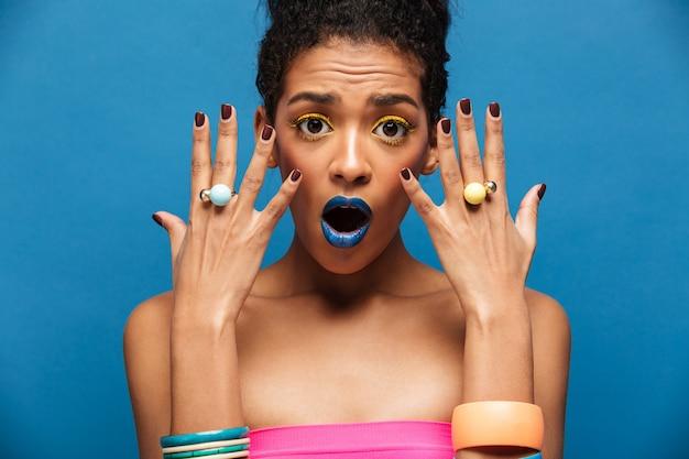 Schoonheidsportret van afro amerikaanse vrouw met maniermake-up die emotioneel juwelen op handen aantonen die camera, over blauwe muur bekijken