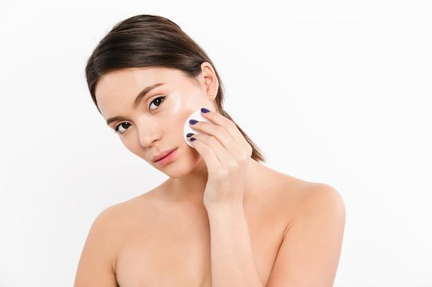 Schoonheidsportret van donkerbruine vrouw die met zachte gezonde huid make-up met katoenen stootkussen verwijderen, dat over wit wordt geïsoleerd
