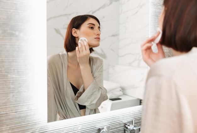 Schoonheidsportret van donkerbruine vrouw die met zachte gezonde huid make-up met katoenen stootkussen verwijderen, in hotelbadkamers
