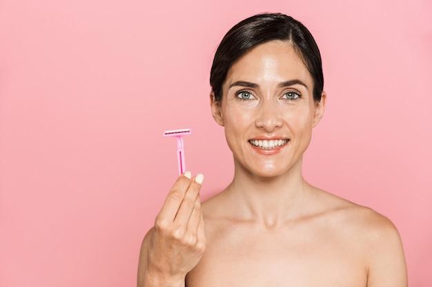 Schoonheidsportret van een aantrekkelijke, gelukkige jonge topless vrouw die geïsoleerd over een roze muur staat en scheermes vasthoudt