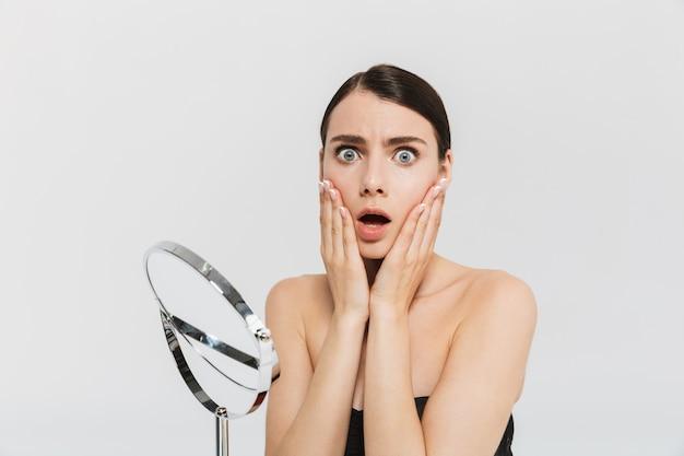 Schoonheidsportret van een aantrekkelijke geschokte jonge donkerbruine vrouw die geïsoleerd over witte muur staat en de huid met spiegel onderzoekt