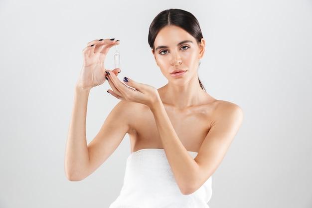Schoonheidsportret van een aantrekkelijke gezonde vrouw die zich geïsoleerd over witte muur bevindt, die een glascapsule met vloeistof toont