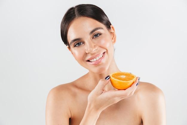 Schoonheidsportret van een aantrekkelijke gezonde vrouw die zich geïsoleerd over witte muur bevindt, die met de helft van een sinaasappel stelt